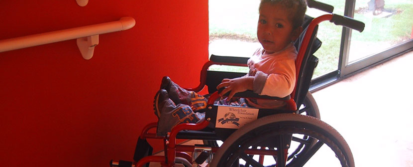 Small boy in wheelchair by red wall